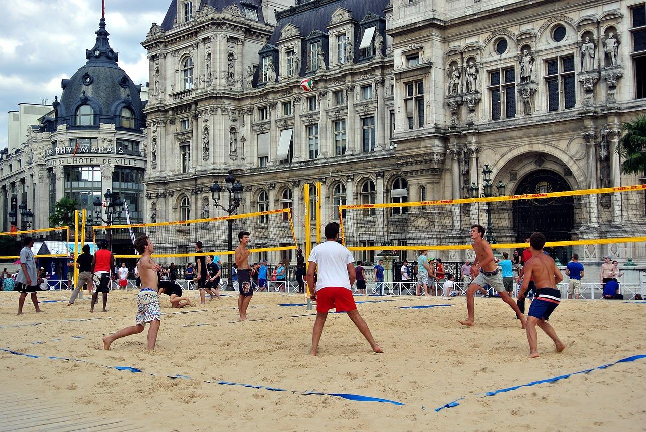 L'origine du beach volley (un peu romancée) Le beach volley est le petit frère du volley-ball indoor (ou d'intérieur). Contrairement au volley indoor ce sport se joue en plein air et comporte quelques aménagements bien spécifiques qui le rendent tout aussi amusant que spectaculaire. Ne serait ce que parce qu'il se joue sur du sable, il donne l'occasion à tous les joueurs et joueuses de plonger au sol pour se rouler dedans. Ne croyez pas que c'est anecdotique ! C'est tellement fréquent que c'est devenu le logo officiel du beach volley (une personne en train de plonger). Ce sport est né durant l'été 1920 (ce devait être un mardi matin sur le coup de 10 h 30). En été traditionnellement, les clubs de volley ferment leurs portes, les compétitions s'arrêtent et le soleil se lève. Les joueurs et joueuses se retrouvaient alors seul(e)s, désespéré(e)s et hagard(e)s. Plus de sport plus de matchs. Certains témoignages de l'époque remontent que l'on croisait des personnes qui marchaient sans but en parlant à leur ballon. C'est sans doute ainsi que les 2 premiers joueurs/joueuses de beach se sont rencontrés, via une collision sur le sable. - aie - mais aie ! - HEY ! Mais c'est un ballon de volley que tu as là (faut imaginer le regard de l'autre qui s'allume à ce moment là) - mais OUI ! Pourquoi ? tu joues au volley ? (un autre regard qui s'illumine) - OUI ! (le ton est plein d'espoir) - Cela te dirait de faire des balles (les 2 personnes commencent à sauter sur place empreints d'une joie frénétique) - OUIIIIIIIIIIIIIII ! (toute cette pression accumulée, tout cet espoir relâché d'un coup... ça devait être beau à voir) Un premier échange s'ensuit, d'autres personnes arrivent et le premier filet de pêche entre 2 arbres sera tendu à peine quelques jours plus tard. Le beach volley était né. Ils se matchèrent et eurent tout plein de sable. Oui c'est une belle histoire ! Et je suis ému à chaque fois que je la raconte. Depuis ses débuts le beach volley à énormément évolué. Tant et si bi